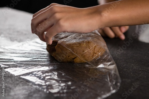 Poster Woman wrapping dough in a plastic wrap