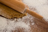 Flattening dough with rolling pin with sprinkled over flour on a - 179023971