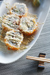Sushi california rolls with topping mayonnaise on ellipse white plate on mat and chopstick beside