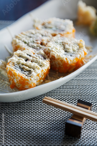 Fotobehang Sushi bar Sushi california rolls with topping mayonnaise on ellipse white plate on mat and chopstick beside