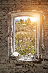 A view from a window hole of an old dilapidated abandoned house.