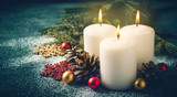 Three Christmas burning candles and decorations on dark turquoise background - 179058175