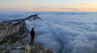 A man looking over a sea of clouds in the mountains at dawn. Vercors, France.