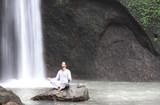 Man sitting in meditation yoga on rock at waterfall Tibumana