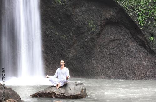Man sitting in meditation yoga on rock at waterfall Tibumana - 179071567