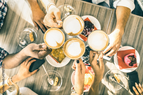 Wall mural Friends group drinking cappuccino at coffee bar restaurant - People hands toasting at fashion cafeteria with upper view point - Winter drinks concept with men and women at cafe - Warm vintage filter