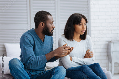 Kind calm man explaining the situation to his girlfriend
