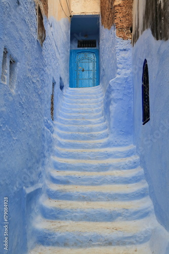 Poster Smal steegje Blue door at the end of a narrow alley with steps, in Chaouen, Morocco