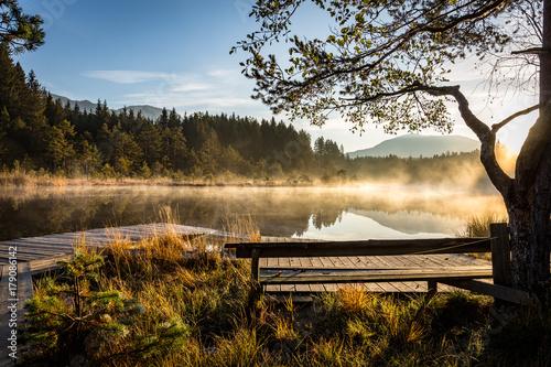 Fotobehang Zwart Sonne scheint am Morgen am See im Herbst