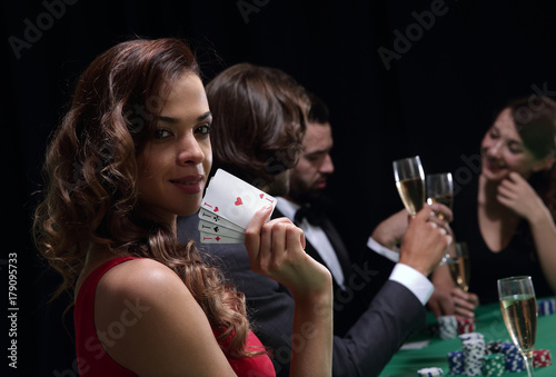 Woman at roulette table holding champagne glass in casino плакат