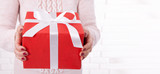 Woman holding Christmas present. Gift box with ribbon. - 179114745