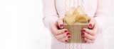 Woman holding Christmas present. Gift box with ribbon. - 179114760