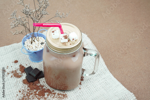 Foto op Aluminium Milkshake chocolate milk or cocoa with chocolate or cocoa ground beans on wooden background