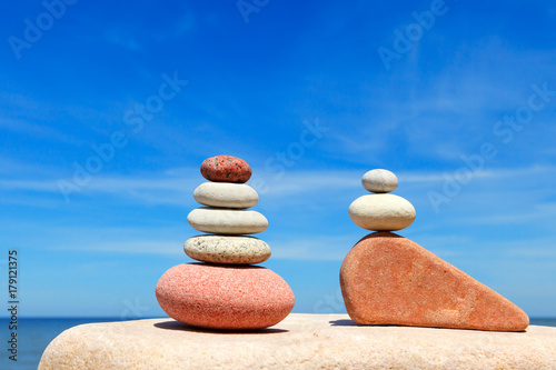 Fotobehang Zen Stones balance on a background of blue sky and sea