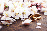 Wedding rings. Spring. Flowering branch on wooden surface. - 179121776