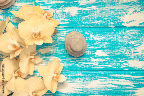 Fotobehang Spa Yellow Orchid with stones on blue background