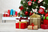 Christmas tree with present boxes over white brick wall - 179125500