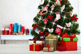Christmas tree with present boxes over white brick wall - 179125519