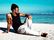 Portrait of handsome hipster sunbathed fashion man model wearing casual clothes in black T-shirt and sunglasses sitting on white sand near blue ocean and sky background