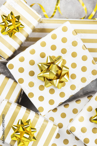 Group of gifts in white and gold paper on a gray background
