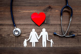 Take out health insurance for family. Stethoscope, paper heart and silhouette of family on wooden background top view - 179141787