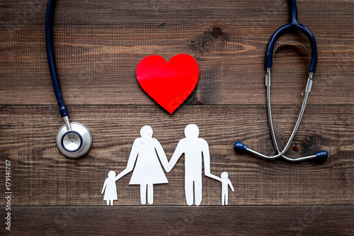 Foto Murales Take out health insurance for family. Stethoscope, paper heart and silhouette of family on wooden background top view