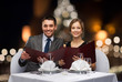 smiling couple with menus at christmas restaurant