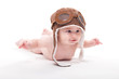 Quadro Naked cute smiling baby in the cap of the pilot is flying on a white background