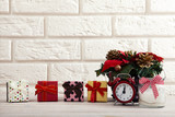 Christmas background. Watch the candle and Christmas tree on a wooden table next to white wall. - 179157585