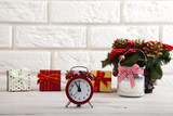 Christmas background. Watch the candle and Christmas tree on a wooden table next to white wall. - 179157720
