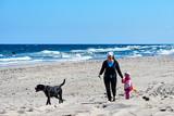 Kobieta spaceruje po plaży w wietrzny dzień z dużym czarnym psem i dzieckiem. - 179159575
