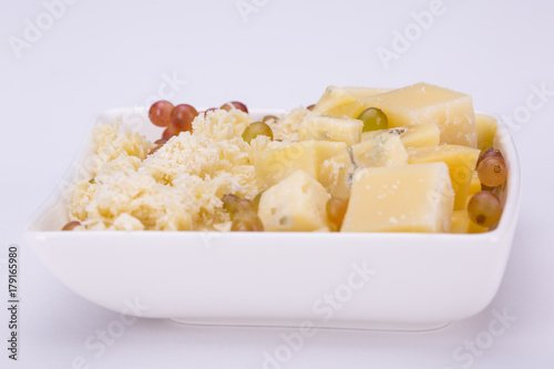 Set of cheeses and grapes on a white background плакат
