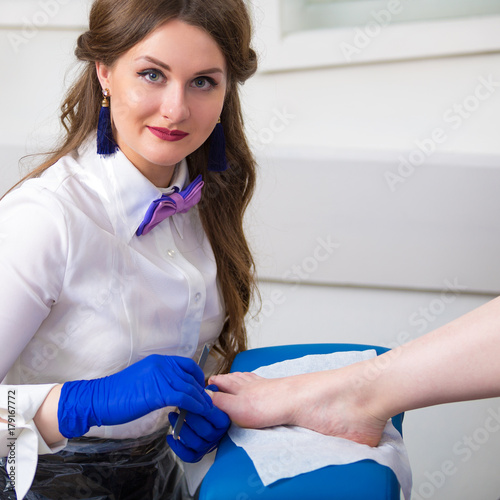 Fotobehang Pedicure A woman is doing a pedicure in a beauty salon. Caring for the legs