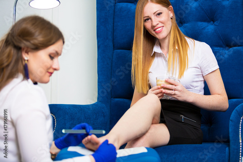 Tuinposter Pedicure A woman is doing a pedicure in a beauty salon. Caring for the legs
