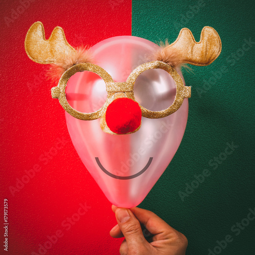 Aluminium Hipster Hert Hand holding Christmas glasses that decoration with reindeer and red hat on air bolloon on green and red background
