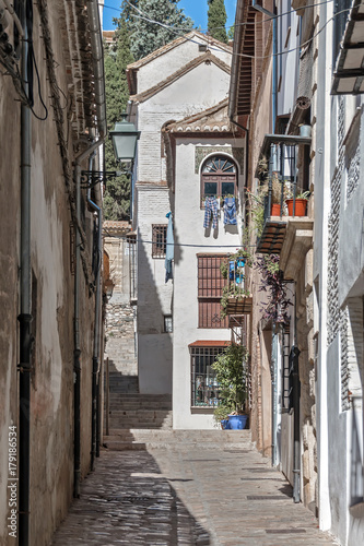Poster Smal steegje Old narrow street perspective at Albayzin district in Granada city, Spain