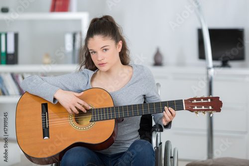 young woman on the wheelchair playing guitar Poster