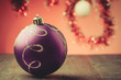 violet Christmas ball on a red light background/violet Christmas ball on a red light background. Selective focus