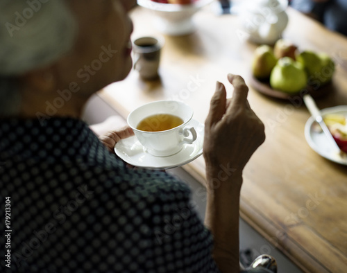 Rear view of senior asian woman holding tea cup talking with friends