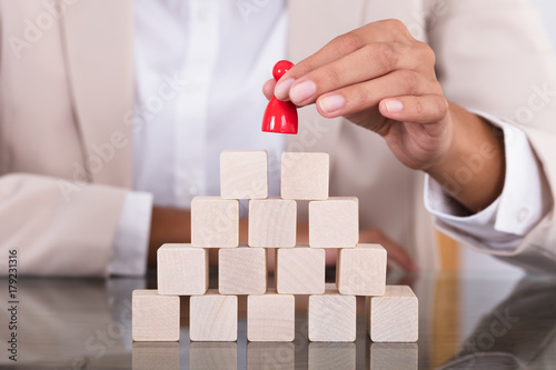 Poster Businesswoman Placing Red Figure On Arranged Blocks