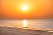 Sunset on the beach with long coastline, sun and dramatic sky