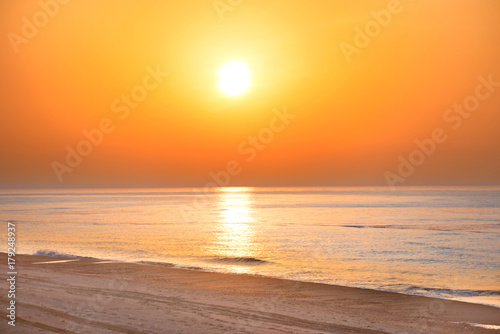 Foto op Plexiglas Zee zonsondergang Sunset on the beach with long coastline, sun and dramatic sky