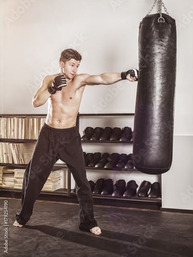 a young man at the punch bag Poster