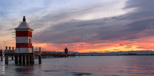 Staande foto Stockholm Beautiful sunrise at the seaside in Italy, at Lignano Sabbiadoro, with pier and lighthouse in the foreground.