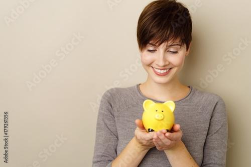 lächelnde frau hält ein sparschwein in händen © contrastwerkstatt
