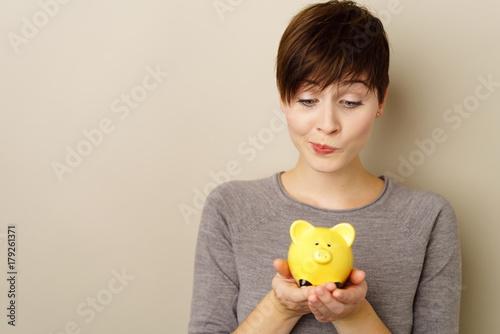 nachdenkliche frau schaut auf ihr sparschwein © contrastwerkstatt