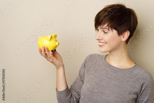 frau schaut ihr sparschwein ein und lächelt © contrastwerkstatt
