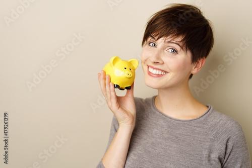 lächelnde frau hält ihr sparschwein in der hand © contrastwerkstatt