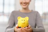 glückliche frau hält ein kleines gelbes sparschwein in den händen - 179261701