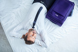 Tired businessman lying on bed in hotel room after arriving on business trip - 179276534